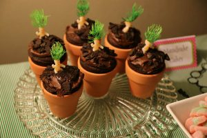 """Mandrake babies. Tiny toy babies with green plant-like hair """"growing"""" in a little flower pot"""
