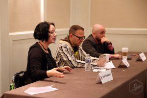 Three panelists, including Eva Galperin, at long table