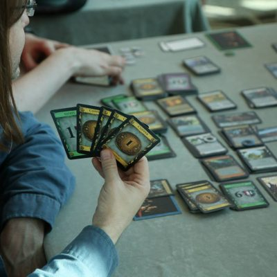 A person with a hand of cards to the camera playing the game Dominion