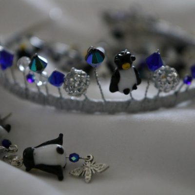 A closeup of a tiara with blue beads and penguin charms