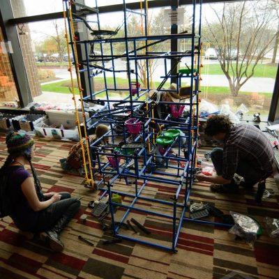 Giant marble machine being worked on by four people