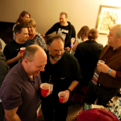 Crowded room party with 13 Penguicon-goers, most holding drinks