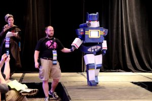 A volunteer holding the hand of a great transformers cosplayer as they walk the runway at the cosplay contest