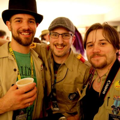 Three Penguicon-goers in tan shirts, one wearing a top hat