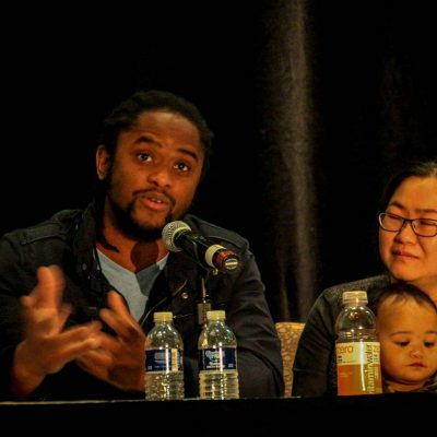Two panelists, one with a tiny human on their lap