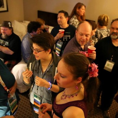 A crowded party in a hotel room with 12 people, many of whom are holding drinks in plastic cups