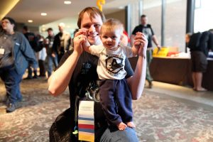 Penguicon-goer with tiny human who is wearing a Penguicon shirt